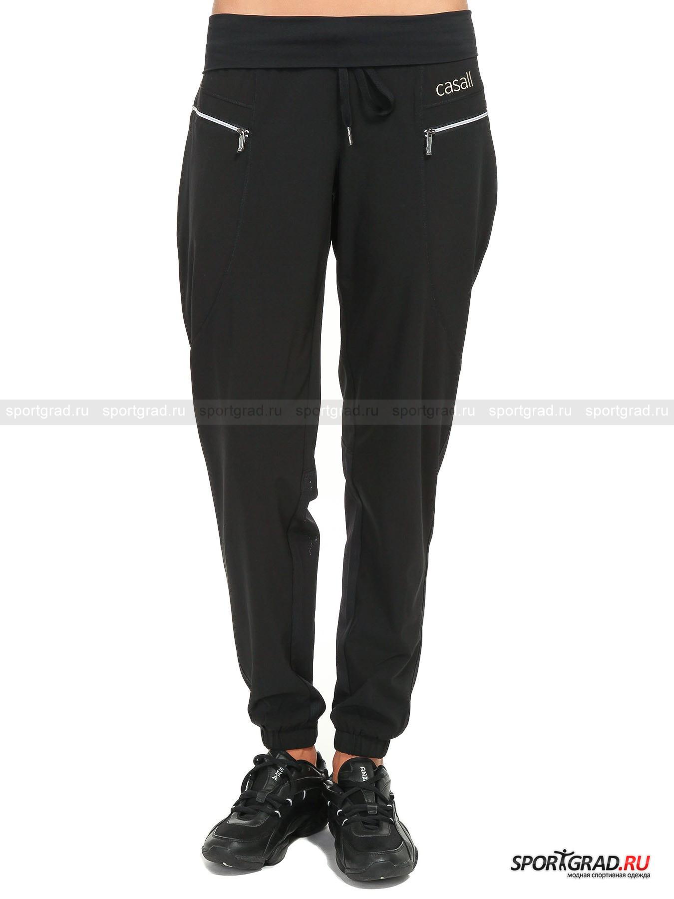 Брюки женские свободные Turf pant CASALL для спорта и танцевБрюки<br>Женские брюки Turf pant CASALL свободного фасона с подвернутым наружу мягким эластичным поясом на кулиске за счет сектора с вентиляционными каналами на голени будет выводить наружу испарину, охлаждая кожу во время занятий спортом и танцами. Ткань с эффектом стрейч гарантирует сохранение амплитуды любого из Ваших движений.<br><br>Модель имеет:<br>- прочную конструкцию рельефных швов спереди и сзади для суперкомфортной посадки;<br>- прочные манжеты с резинкой внутри;<br>- два кармана на бедрах с застежкой на молнию.<br>Длина изделия по боковому шву с учетом манжет и развернутого поса 101 см, ширина в бедрах 52 см (размер 38).<br><br>Пол: Женский<br>Возраст: Взрослый<br>Тип: Брюки<br>Рекомендации по уходу: Изделию показана стирка при температуре строго 40°, глажка при температуре, не превышающей 110°, и химчистка. Запрещены отбеливание и сушка в стиральной машине и электросушилке для белья.<br>Состав: 93% полиэстер, 7% эластан