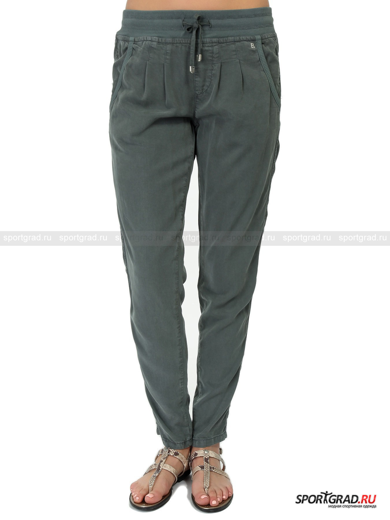 Брюки женские из лиоцелла Sarouel Pants BOGNER JEANSБрюки<br>Симпатичные брюки самого модного в этом сезоне серо-зеленого цвета Sarouel Pants от Bogner Jeans – идеальный выбор в жаркую погоду. Они пошиты из уникального материала лиоцелл, прекрасно подходящего для лета: он превосходно пропускает воздух, позволяя коже дышать, и отлично впитывает влагу, быстро испаряя ее с поверхности. Благодаря этому сохраняется постоянная комфортная температуру тела. Материал является экологически чистым, он не мнется, не нуждается в особом уходе и отличается повышенной прочностью.<br><br>Особенности модели:<br>- пояс на резинке с кулиской и регулирующей лентой;<br>- два кармана по бокам;<br>- сзади карманы-«обманки»;<br>- фирменная нашивка-логотип.<br><br>Пол: Женский<br>Возраст: Взрослый<br>Тип: Брюки<br>Рекомендации по уходу: стирка при температуре до 30 С; не отбеливать; гладить слегка нагретым утюгом (температура до 110 C); химчистка запрещена; нельзя сушить в стиральной машине<br>Состав: 100% лиоцелл